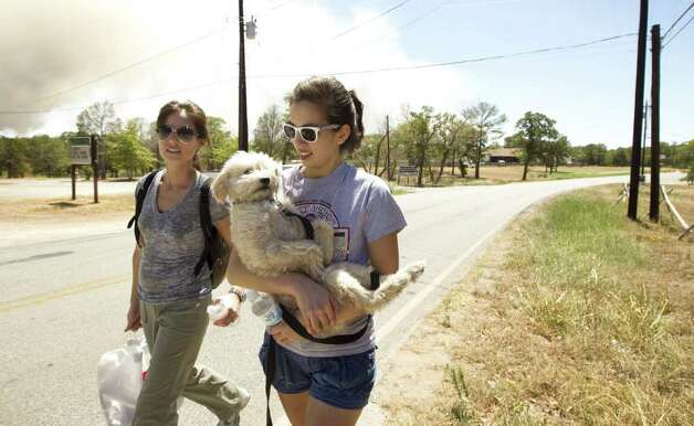 Paula Wilson, left, and her sister Monica Wilson walk along Tahitian Drive in Bastrop, Texas, after rescuing  their father's dog, Homer, on Monday Sept. 5, 2011.  Their father was forced to evacuate from his home as fire neared the area. A roaring wildfire raced unchecked Monday through rain-starved farm and ranchland in Texas, destroying nearly 500 homes during a rapid advance fanned in part by howling winds from the remnants of Tropical Storm Lee. (AP Photo/Austin American-Statesman, Jay Janner)  Photo: Jay Janner, Associated Press / Austin American-Statesman