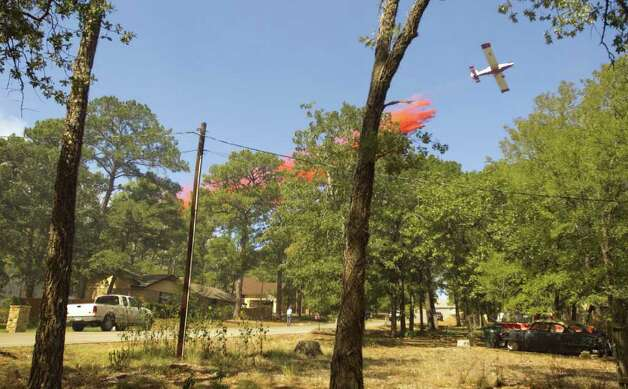 A plane drops fire retardant on a house on Mauna Kea Lane in the Tahitian Village neighborhood in Bastrop, Texas,  on Monday Sept. 5, 2011. A house on the street was burned to the ground. A roaring wildfire raced unchecked Monday through rain-starved farm and ranchland in Texas, destroying nearly 500 homes during a rapid advance fanned in part by howling winds from the remnants of Tropical Storm Lee. (AP Photo/Austin American-Statesman, Jay Janner)  Photo: Jay Janner, Associated Press / Austin American-Statesman