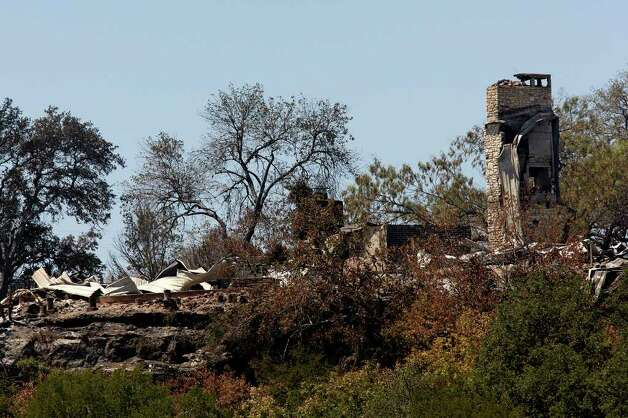 The remains of a house destroyed by a wildfire in the Paleface Rancharea off State Highway 71 near Spicewood, Texas, are seen on a bluff, Monday, Sept. 5, 2011. JERRY LARA/glara@express-news.net Photo: JERRY LARA, San Antonio Express-News / SAN ANTONIO EXPRESS-NEWS