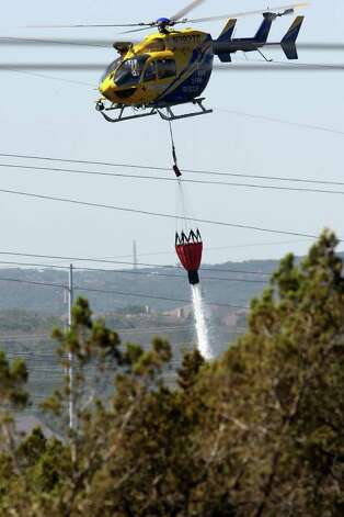 Emergency personnel battle a wildfire in the Steiner Ranch subdivision in western Travis County, Monday, Sept. 5, 2011. JERRY LARA/glara@express-news.net Photo: JERRY LARA, San Antonio Express-News / SAN ANTONIO EXPRESS-NEWS