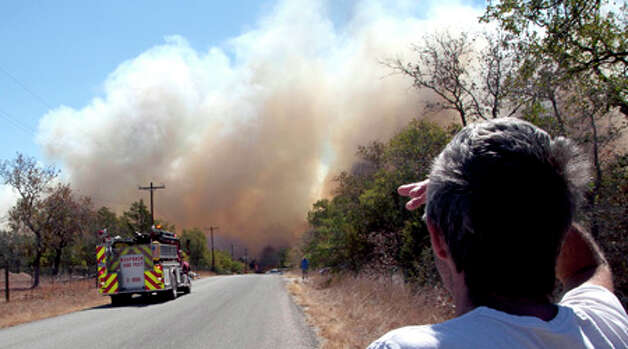 CORRECTS SECOND SENTENCE OF CAPTION  Local resident George Harris looks on from a safe distance as firefighters attempt to control a blaze in Cedar Park, Texas  on Monday, Sept. 5, 2011.  A roaring wildfire raced unchecked Monday through rain-starved farm and ranchland in Texas, destroying nearly 500 homes during a rapid advance fanned in part by howling winds from the remnants of Tropical Storm Lee.   (AP Photo/The Daily Texan, Thomas Allison) Photo: Thomas Allison, Associated Press / Thomas Allison