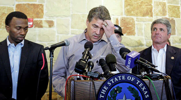 Gov. Rick Perry, center, holds a news conference to discuss wild fires in central Texas, Monday, Sept. 5, 2011, in Bastrop, Texas.  A roaring wildfire raced unchecked Monday through rain-starved farm and ranchland in Texas, destroying nearly 500 homes during a rapid advance fanned in part by howling winds from the remnants of Tropical Storm Lee. (AP Photo/Eric Gay) Photo: Eric Gay, Associated Press / AP