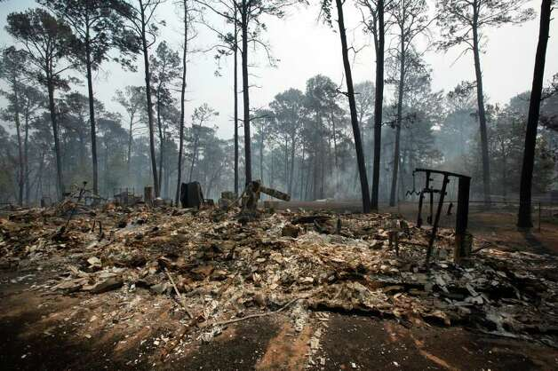 Remnants of a burned out home off Highway 71 near Bastrop, Texas as a series of large wildfires continue to burn Monday, Sep. 5, 2011.  A roaring wildfire raced unchecked Monday through rain-starved farm and ranchland in Texas, destroying nearly 500 homes during a rapid advance fanned in part by howling winds from the remnants of Tropical Storm Lee.  (AP Photo/Erich Schlegel) Photo: Erich Schlegel, Associated Press / FR 62355 AP