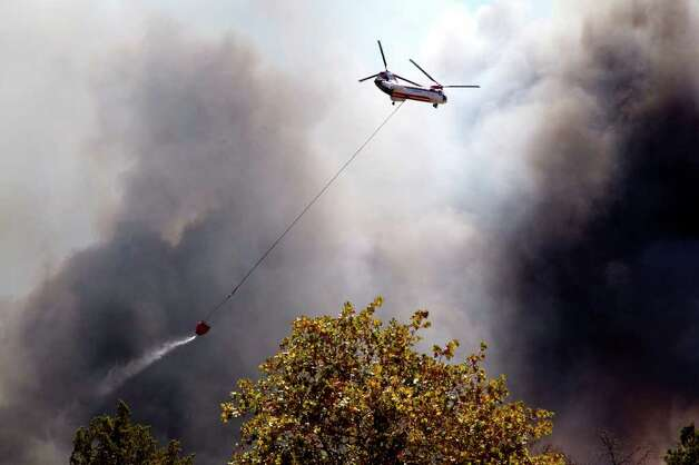 A helicopter drops water onto a blaze in Cedar Park,   Texas  on Monday, Sept. 5, 2011.    A roaring wildfire raced unchecked Monday through rain-starved farm and ranchland in Texas, destroying nearly 500 homes during a rapid advance fanned in part by howling winds from the remnants of Tropical Storm Lee.   (AP Photo/The Daily Texan, Thomas Allison ) Photo: Thomas Allison, Associated Press / Thomas Allison