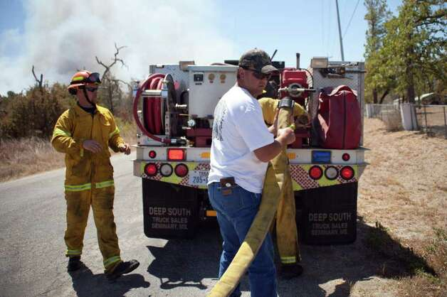 Jeffery Whited, a volunteer, helps fire fighters hook up a hose to their tank trunk before they head out to fight the wildfire raging through Bastrop County, Texas  on Monday, Sept. 5, 2011.    A roaring wildfire raced unchecked Monday through rain-starved farm and ranchland in Texas, destroying nearly 500 homes during a rapid advance fanned in part by howling winds from the remnants of Tropical Storm Lee.   (AP Photo/The Daily Texan, Trent Lesikar ) Photo: Trent Lesikar, Associated Press / Trent Lesikar | The Daily Texan