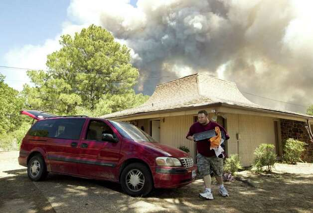 Ryan Joseph Terranova packs up his belongings moments before evacuating his home   in Bastrop, Texas, as a huge fire approaches  on Monday Sept. 5, 2011.  A roaring wildfire raced unchecked Monday through rain-starved farm and ranchland in Texas, destroying nearly 500 homes during a rapid advance fanned in part by howling winds from the remnants of Tropical Storm Lee. (AP Photo/Austin American-Statesman, Jay Janner)  MAGS OUT; NO SALES; TV OUT; INTERNET OUT EXCEPT AP MEMBERS Photo: Jay Janner, Associated Press / Austin American-Statesman