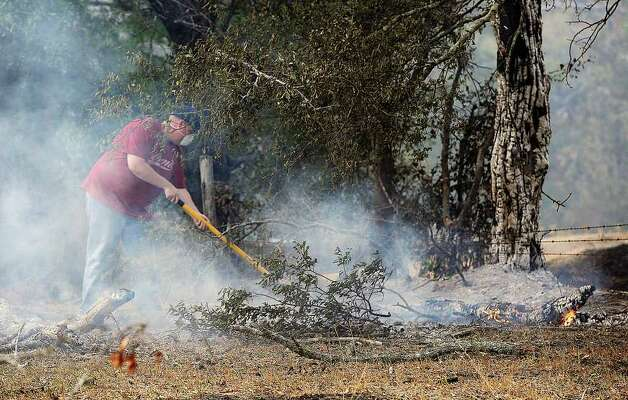 A man,  uses a shovel to extinguish flames Monday, Sept. 5, 2011, near Lilbert, Texas.  A roaring wildfire raced unchecked Monday through rain-starved farm and ranchland in Texas, destroying nearly 500 homes during a rapid advance fanned in part by howling winds from the remnants of Tropical Storm Lee.   (AP Photo/The Daily Sentinel, Andrew D. Brosig) MANDATORY CREDIT Photo: Andrew D. Brosig, Associated Press / THE DAILY SENTINEL