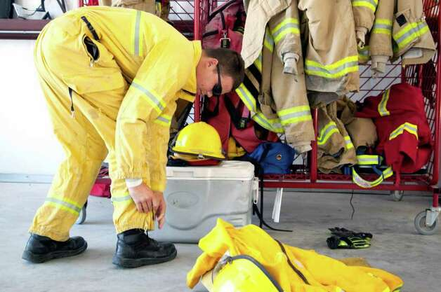 Steven Smith of the Weir Fire Department dons protective clothing in the Bluebonnet Volunteer Fire Department station in Cedar Park, Texas on Monday, Sept. 5, 2011.  Monday, Sept. 5, 2011.   A roaring wildfire raced unchecked Monday through rain-starved farm and ranchland in Texas, destroying nearly 500 homes during a rapid advance fanned in part by howling winds from the remnants of Tropical Storm Lee.   (AP Photo/The Daily Texan, Thomas Allison) Photo: Thomas Allison, Associated Press / Thomas Allison