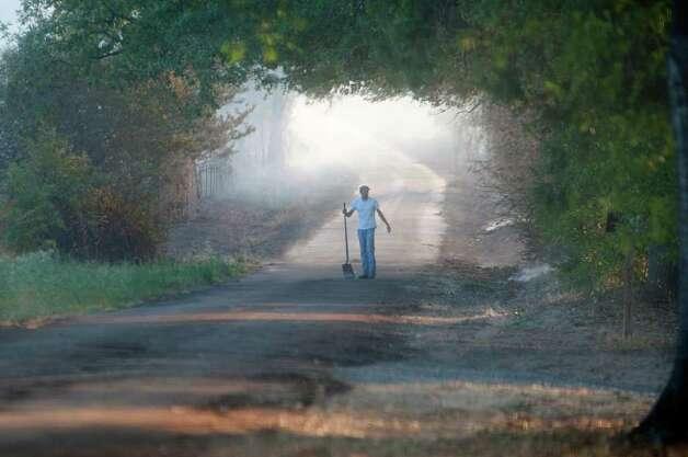A resident carries a shovel to pat down smolders during a 7,000 acre fire in southern Cass County, Texas Monday, Sept. 5, 2011. (AP Photo/The Texarkana Gazette, Christena Dowsett) Photo: Christena Dowsett, Associated Press / Texarkana Gazette