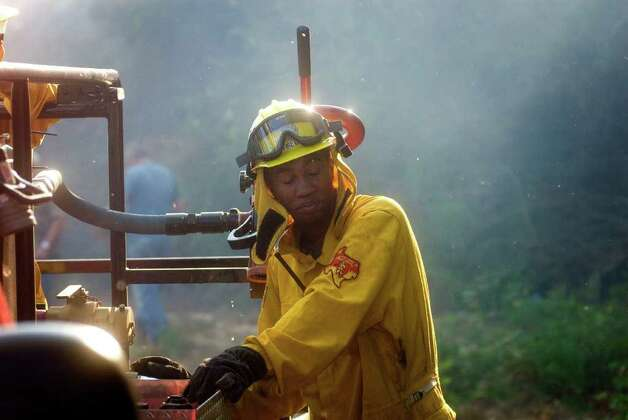 A Maud, Texas firefighter closes his eyes to avoid fire debris during a 7,000 acre fire in southern Cass County, Texas Monday, Sept. 5, 2011. (AP Photo/The Texarkana Gazette, Christena Dowsett) Photo: Christena Dowsett, Associated Press / Texarkana Gazette