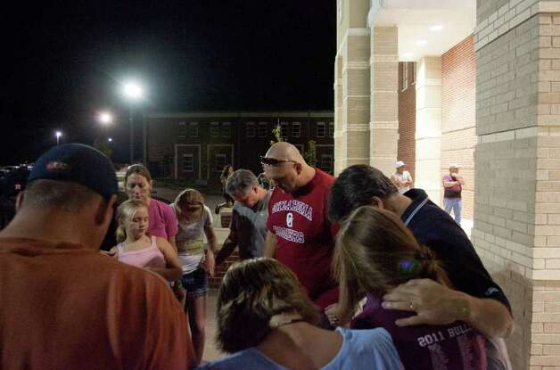 Jack Novak, in red, head pastor with The Grove church, leads a prayer outside Magnolia High School where residents evacuated from their homes near  a 300-acre wild fire gathered Monday, Sept. 5, 2011 in Magnolia, Texas. Nearly 8,000 residents were evacuated from their homes. (AP Photo/The Courier, Eric S. Swist) Photo: Eric S. Swist, MBR / AP
