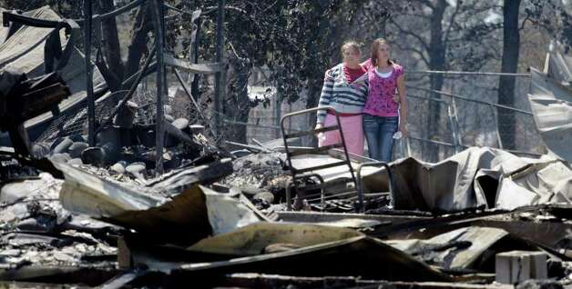 Sisters Laura, left, and Michelle Clements survey their fire-destroyed home, Tuesday, Sept. 6, 2011, in Bastrop, Texas. The Clements lost their home to fires Monday. (AP Photo/Eric Gay) Photo: Eric Gay, STF / Copyright 2011 The Associated Press. All rights reserved. This material may not be published, broadcast, rewritten or redistribu