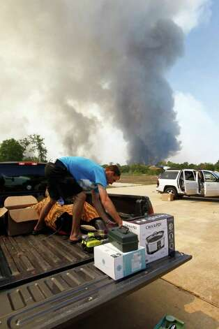 Charlie Brown helps friends evacuate as winds change the direction of a fire, Tuesday, Sept. 6, 2011, in Montgomery County, Texas.   More than 1,000 homes have been destroyed in at least 57 wildfires across rain-starved Texas, most of them in one devastating blaze near Austin that is still raging out of control, officials said Tuesday.  ( AP Photo/Houston Chronicle, Nick de la Torre) MANDATORY CREDIT Photo: Nick De La Torre, MBO / © 2011 Houston Chronicle