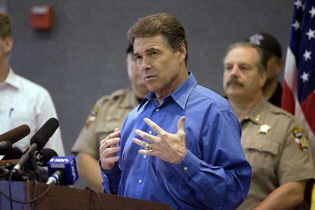 Texas Gov. Rick Perry speaks  to media after tasking an aerial tour of the fire devastation at Steiner Ranch, a residential development in Austin, Texas.  (AP Photo/Austin American-Statesman, Alberto MartInez )  MAGS OUT; NO SALES; TV OUT; INTERNET OUT; AP MEMBERS ONLY Photo: Alberto MartInez, MBR / Austin American-Statesman