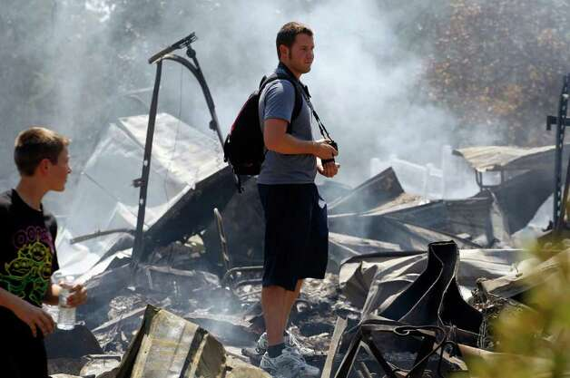 Brothers Ben, left, and Nathan Clements survey their fire-destroyed home, Tuesday, Sept. 6, 2011, in Bastrop, Texas. The Clements lost their home to fires Monday. (AP Photo/Eric Gay) Photo: Eric Gay, STF / AP