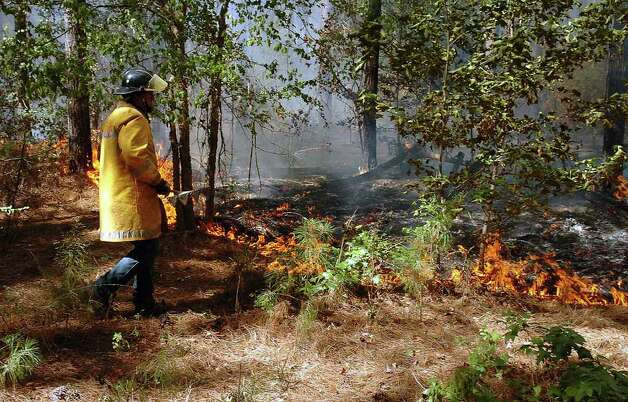 A Cushing, Texas, firefighter approaches a section of the front line of a massive wildfire on Tuesday, Sept. 6, 2011, near Lilbert, Texas. The Texas Forest Service estimated the fire, one of several throughout the state, had burned an estimated 2,600 acres as of Wednesday morning. (AP Photo/The Daily Sentinel, Andrew D. Brosig) Photo: Andrew D. Brosig, MBR / The Daily Sentinel