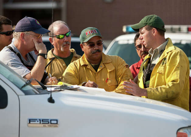 Texas Forest Service firefighters discuss the movement of a 1,600-acre wild fire Tuesday, Sept. 6, 2011 at a command center in Magnolia, Texas. (AP Photo/The Courier, Eric S. Swist) / AP
