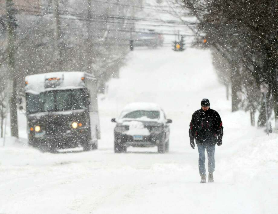 A man walks on East Elm Street in the snowstorm that hit Greenwich, Conn., Thursday, Feb. 13, 2014. The National Weather Service is forecasting a total possible accumulation of 10 inches of snow by the time the storm ends Friday morning. Photo: Bob Luckey / Greenwich Time