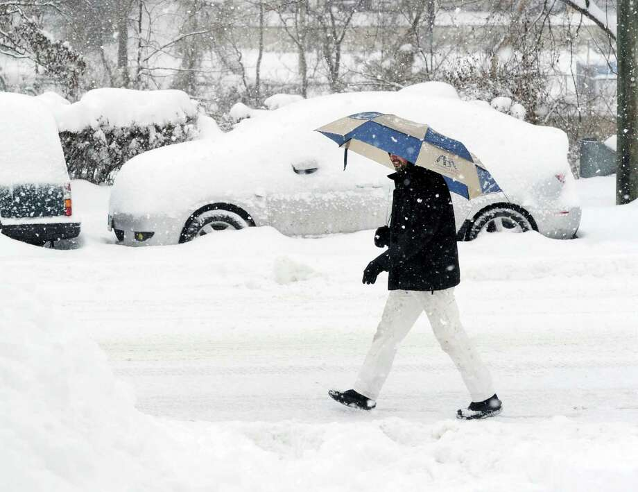 A man uses an umbrella while walking on Byram Road during the snowstorm that hit Greenwich, Conn., Thursday, Feb. 13, 2014. The National Weather Service is forecasting a total possible accumulation of 10 inches of snow by the time the storm ends Friday morning. Photo: Bob Luckey / Greenwich Time