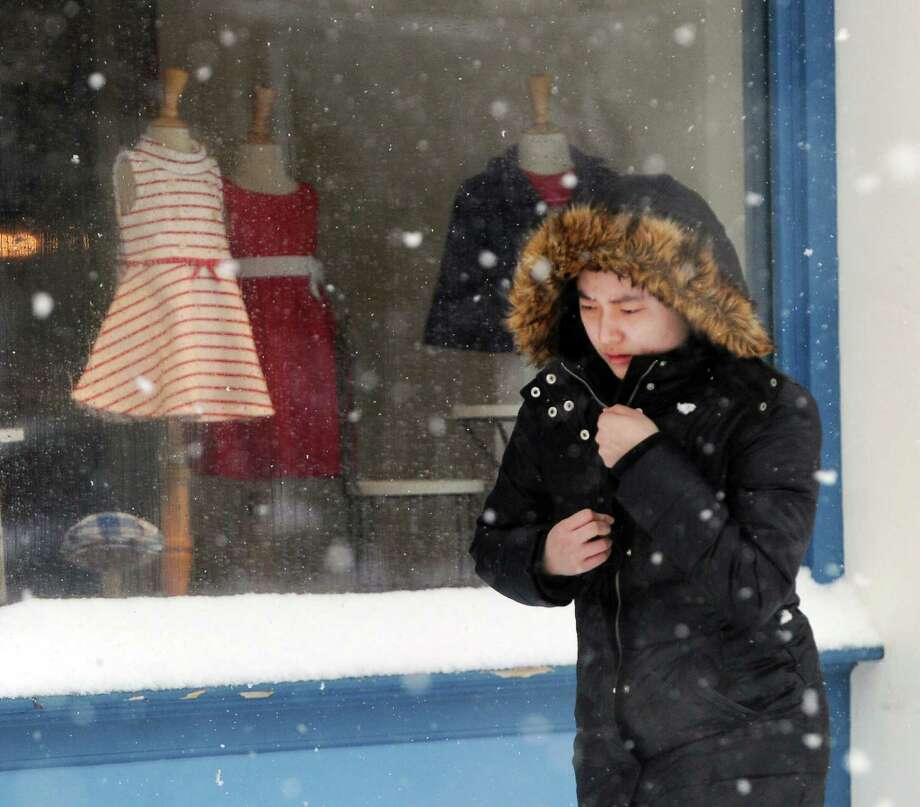 A woman walks on Greenwich Avenue during the snowstorm that hit Greenwich, Conn., Thursday, Feb. 13, 2014. The National Weather Service is forecasting a total possible accumulation of 10 inches of snow by the time the storm ends Friday morning. Photo: Bob Luckey / Greenwich Time