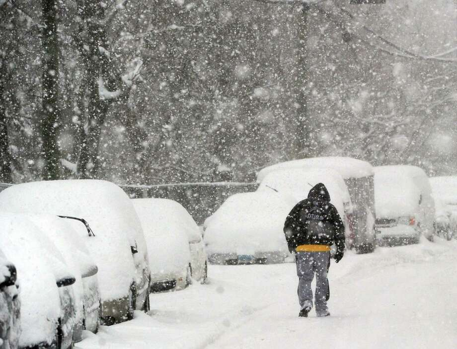 A man walks along Byram Road during the snowstorm that hit Greenwich, Conn., Thursday, Feb. 13, 2014. The National Weather Service is forecasting a total possible accumulation of 10 inches of snow by the time the storm ends Friday morning. Photo: Bob Luckey / Greenwich Time