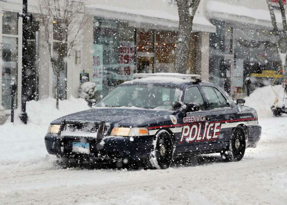 A Greenwich police car makes its way on Greenwich Avenue during the snowstorm that hit Greenwich, Conn., Thursday, Feb. 13, 2014. The National Weather Service is forecasting a total possible accumulation of 10 inches of snow by the time the storm ends Friday morning. Photo: Bob Luckey / Greenwich Time