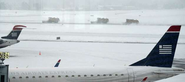 Crews work to clear snow at Albany International Airport Thursday morning, Feb. 13, 2014,  in Colonie, N.Y.   (Skip Dickstein / Times Union) Photo: SKIP DICKSTEIN
