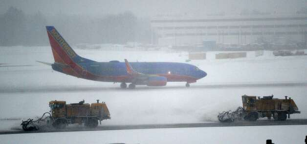 Crews work to clear snow from the taxiway as a Southwest jet prepares for takeoff Thursday morning, Feb. 13, 2014, at Albany International Airport in Colonie, N.Y.   (Skip Dickstein / Times Union) Photo: SKIP DICKSTEIN