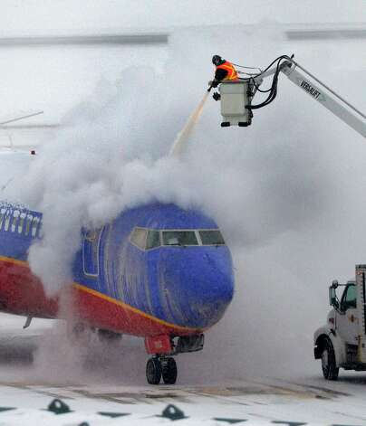 Crews work to clear snow from a departing Southwest 737 jetliner Thursday morning, Feb. 13, 2014, at Albany International Airport in Colonie, N.Y.   (Skip Dickstein / Times Union) Photo: SKIP DICKSTEIN