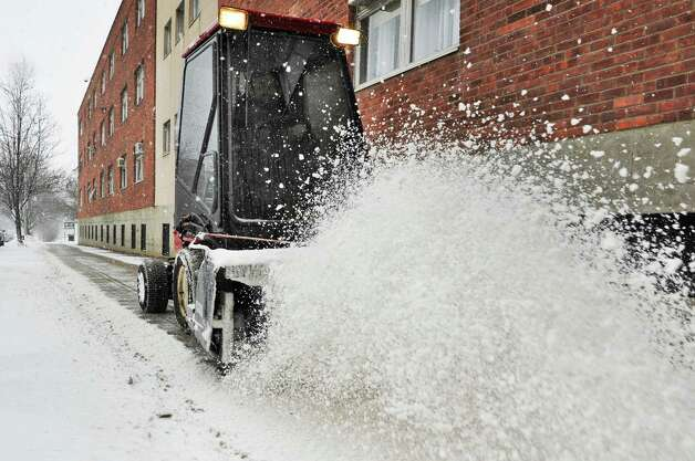 Sage maintenance crew's Doug Gleason clears snow from sidewalks on campus Thursday, Feb. 13, 2014, in Troy, N.Y.   (John Carl D'Annibale / Times Union) Photo: John Carl D'Annibale / 00025747A