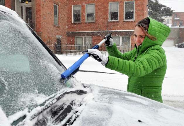 Sage nursing student Nora Munsey clears snow from her car as she leaves campus Thursday Feb. 13, 2014, in Troy, N.Y.   (John Carl D'Annibale / Times Union) Photo: John Carl D'Annibale / 00025747A