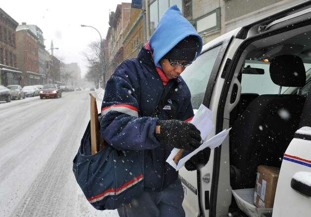 Postal carrier Illandria Graham delivers mail Thursday Feb. 13, 2014, along River Street in Troy, N.Y.   (John Carl D'Annibale / Times Union) Photo: John Carl D'Annibale / 00025747A