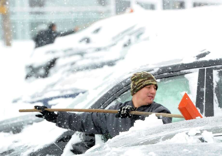 "Julio Sanchez cleans snow from automobiles at a car dealership on Railroad Avenue during the snowstorm that hit Greenwich, Conn., Thursday, Feb. 13, 2014. The National Weather Service is forecasting a total possible accumulation of 10 inches of snow by the time the storm ends Friday morning. Sanchez called the winter ""crazy!"" Photo: Bob Luckey / Greenwich Time"