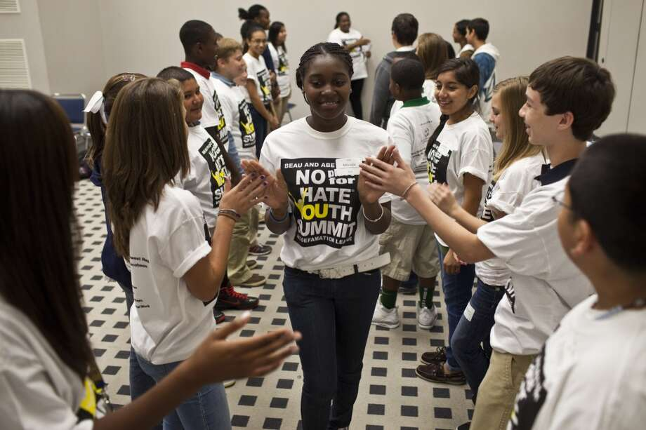 """Mikayla Bailey, 13, high-fives other students during a break out session as nearly 600 Students attended the 2011 Beau and Abe Merfish No Place for Hate  Youth Summit, Oct. 18, 2011 in Houston at the GRB. Children learned tools to help prevent bullying, to recognize it, and to respond to it properly when it happens. Nearly 600 middle school students and 90 educators from public and private campuses watched an anti-bullying play by Dionysus Theatre titled """"True Confessions of a Bully"""". (Eric Kayne/For the Chronicle) Photo: For The Houston Chronicle"""
