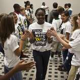 "Mikayla Bailey, 13, high-fives other students during a break out session as nearly 600 Students attended the 2011 Beau and Abe Merfish No Place for Hate  Youth Summit, Oct. 18, 2011 in Houston at the GRB. Children learned tools to help prevent bullying, to recognize it, and to respond to it properly when it happens. Nearly 600 middle school students and 90 educators from public and private campuses watched an anti-bullying play by Dionysus Theatre titled ""True Confessions of a Bully"". (Eric Kayne/For the Chronicle)"
