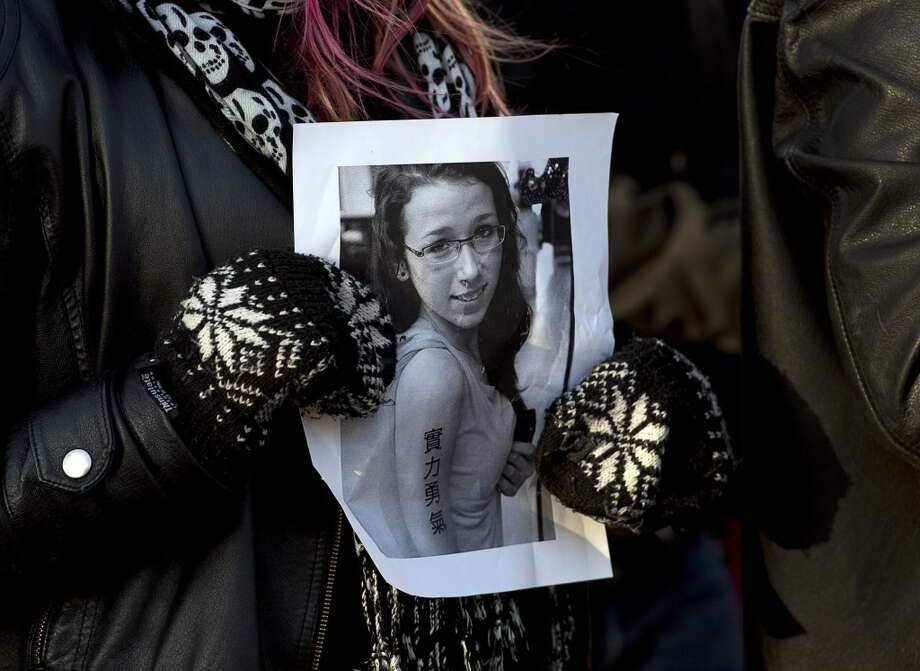 This April 11, 2013 file photo, a woman holds a photo as several hundred people attend a community vigil to remember Rehtaeh Parsons at Victoria Park in Halifax, Nova Scotia, Canada.  Police said Thursday, Aug. 8, 2013,  they have made two arrests in the case of Rehtaeh Parsons, 17, who died after a photo of her allegedly being sexually assaulted was shared online. The death of  Parsons, who was taken off life support after a suicide attempt in April, led to an outcry. Police initially concluded there were no grounds to charge anyone after a year-long investigation. Her mother said a boy took a photo of the alleged assault in 2011 and that her daughter was bullied after it went viral. Royal Canadian Mounted Police Cpl. Scott MacRae said they arrested two males Thursday. Investigators said they are being questioned and no further information will be released at this time. MacRae declined to say what they were arrested for or whether charges are expected. (AP Photo/The Canadian Press, Andrew Vaughan) Photo: Associated Press
