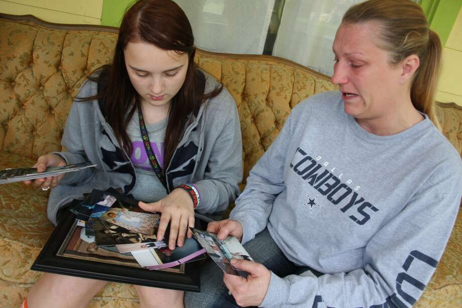 """FILE - In this April 17, 2012, file photo, Kenneth Weishuhn's sister, Kayla Weishuhn, 16, and his mother, Jeannie Chambers, look at photos of Kenneth, 14, who committed suicide April 15 at their home Primghar, Iowa. Chambers said she knew her son was being harassed but that she and the rest of the family didn't realize the extent of the bullying. The Sioux City Journal's front-page opinion piece on its Sunday, April 22 edition calls on the community to be pro-active in stopping bullying and urges members to learn more about the problem by seeing the acclaimed new film, """"Bully,"""" which documents the harassment of Sioux City middle school student. It notes that while many students are targeted for being gay, """"we have learned a bully needs no reason to strike."""" (AP Photo/Sioux City Journal, Laura Wehde) Photo: Associated Press"""