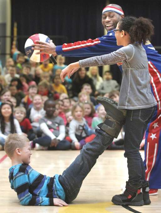 """Harlem Globetrotter Tay """"Firefly"""" Fisher helps Southgate Elementary School students Zoë Cooper, 9, right and Dylan Lettrick, 8, how to make the letter """"C"""" for courage Monday Feb. 10, 2014, as he delivered a message to the Kennewick students on anti-bullying. Fisher taught a group some moves and they performed to the Globetrotter them song """"Sweet Georgia Brown."""" Fisher and the rest of the Globetrotters will be performing Feb. 20 at the Toyota Center in Kennewick, Wash. (AP Photo/Tri-City Herald, Paul T. Erickson) Photo: Associated Press"""