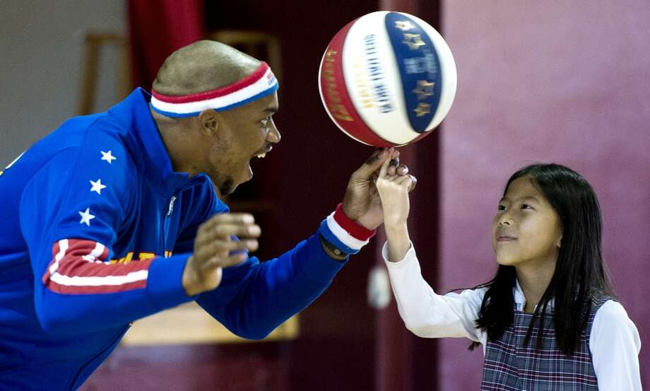 """Harlem Globetrotter John """"Jet"""" Williams, left, spins the ball on the finger of Helena Stafford, a third grade student at John Paul II Catholic School, Wednesday, Jan. 15, 2014, in Overland Park, Kan. Williams was visiting the school with teammate Joyce """"Sweet J"""" Ekworomadu, where they talked to grade school students on the topic of bullying while promoting the Jan. 25 appearance of the Globetrotters at the Sprint Center. (AP Photo/The Kansas City Star, John Sleezer) Photo: Associated Press"""