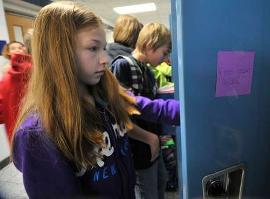 D.C. Everest Middle School student Megan Brummond on Wednesday, Jan. 29, 2014, opens her locker, adorned with a positive message written on a sticky note in Weston, Wis. Notes were placed on students lockers to help create an atmosphere that discourages bullying. (AP Photo/Daily Herald Media, T'xer Zhon Kha) NO SALES. Photo: T'xer Zhon Kha, Associated Press / The Wausau Daily Herald
