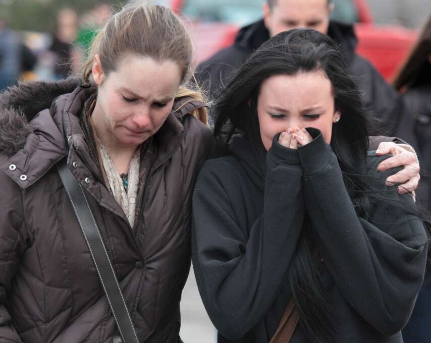 A distraught Ava Polaski, a sophomore, leaves school grounds with her mother Misty Polaski following a shooting in Chardon, Ohio on Monday, Feb. 27, 2012.   A teenager described as a bullied outcast at Chardon High School opened fire in the cafeteria Monday morning, killing one student and wounding four others before being caught a short distance away, authorities said.  The suspect, whose name was not released, was arrested near his car a half-mile away, the FBI said. He was not immediately charged. (AP Photo/The Plain Dealer, Thomas Ondrey) MANDATORY CREDIT Photo: Associated Press