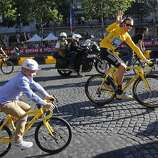 "FILE - In this Sunday July 22, 2012 file photo Bradley Wiggins, winner of the 2012 Tour de France cycling race, rides with his son during the team parade of the the Tour de France cycling race in Paris, France. Former Tour de France champion Bradley Wiggins says he had to find a new school for his children after they were ""harassed and bullied"" following the Lance Armstrong doping scandal. (AP Photo/Laurent Cipriani, File)"