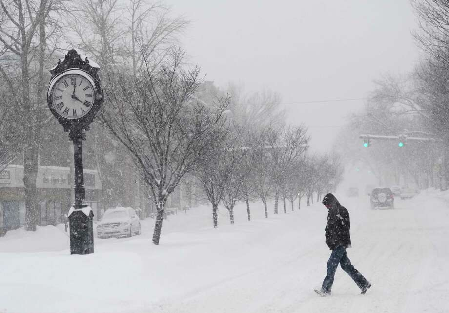 A pedestrian crosses Main Street as snow falls in downtown Danbury, Conn. Thursday, Feb. 13, 2014.  Danbury and its surrounding areas are expected to see 14 to 20 inches of snow, which is expected to taper off around midnight. Photo: Tyler Sizemore / The News-Times