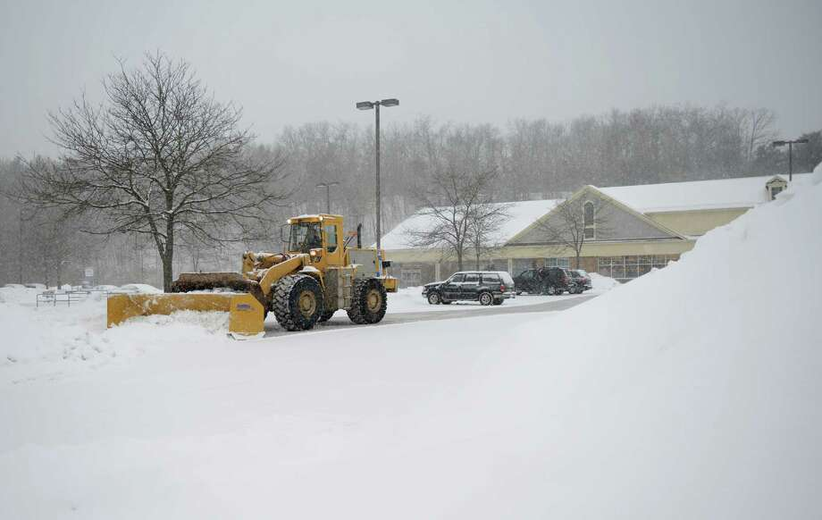 A snowplow clears the Stop & Shop parking lot as snow continues to fall in Newtown, Conn. Thursday, Feb. 13, 2014.  Danbury and its surrounding areas are expected to see 14 to 20 inches of snow, which is expected to taper off around midnight. Photo: Tyler Sizemore / The News-Times