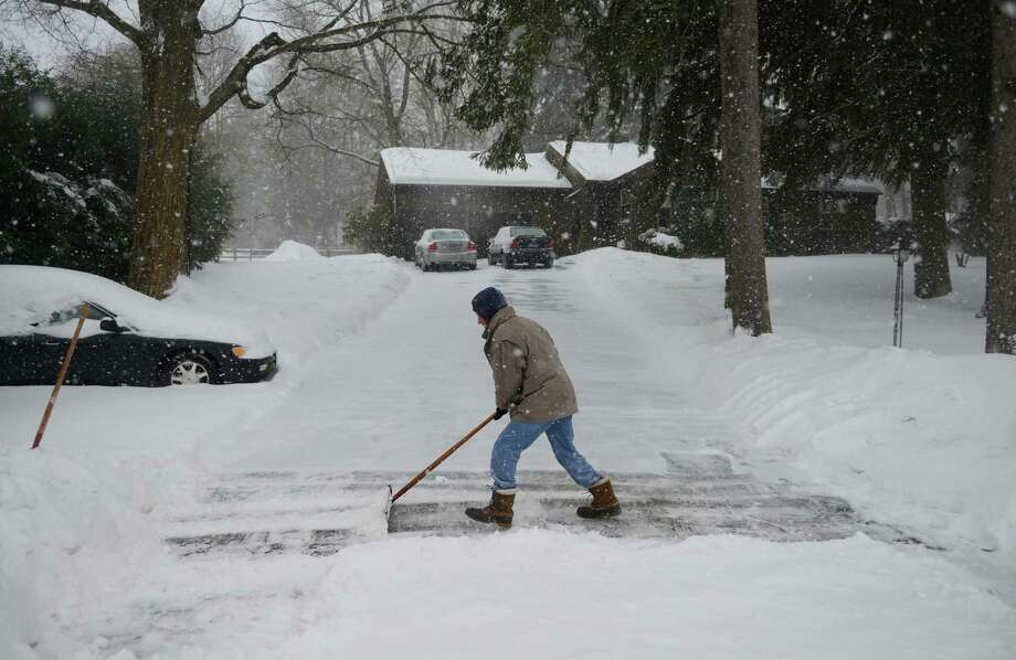 Don Hammond, of Newtown, shovels his driveway as snow continues to fall in Newtown, Conn. Thursday, Feb. 13, 2014.  Danbury and its surrounding areas are expected to see 14 to 20 inches of snow, which is expected to taper off around midnight. Photo: Tyler Sizemore / The News-Times