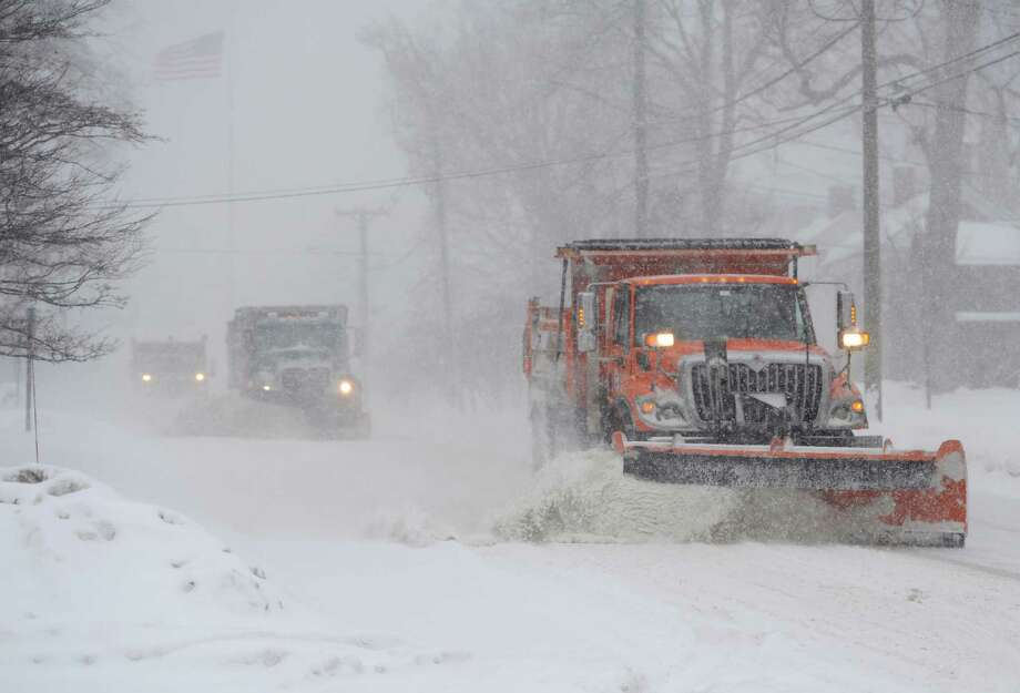 Three plow trucks clear the snow on Main Street as snow continues to fall in Newtown, Conn. Thursday, Feb. 13, 2014.  Danbury and its surrounding areas are expected to see 14 to 20 inches of snow, which is expected to taper off around midnight. Photo: Tyler Sizemore / The News-Times