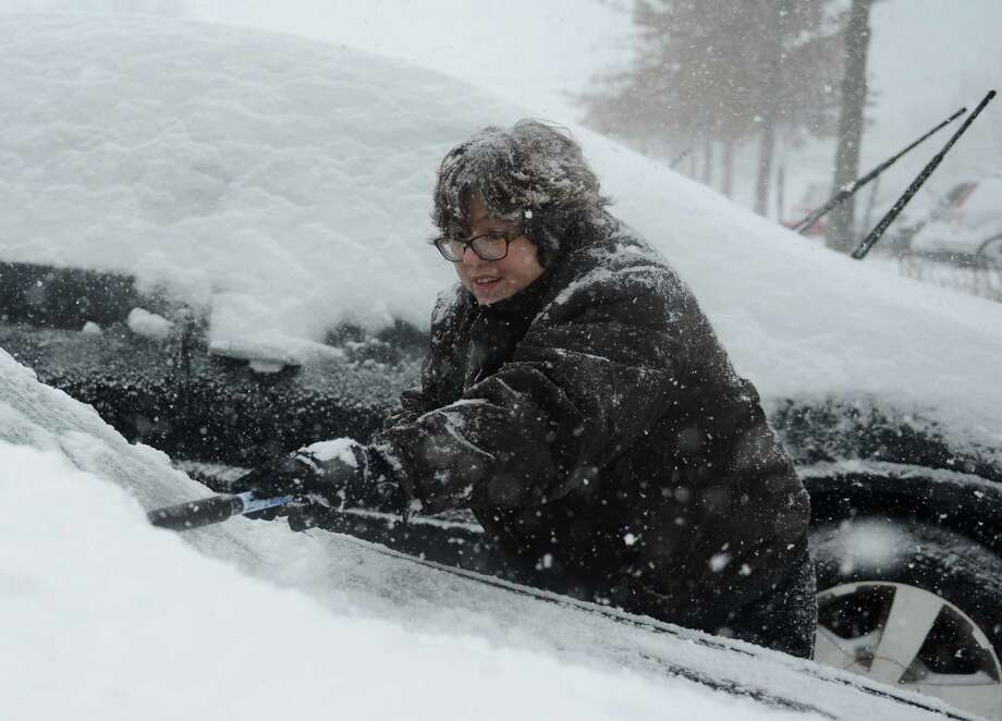 Tiffany Lowe, of Sandy Hook, brushes snow off her car in the Big Y parking lot in Newtown, Conn. Thursday, Feb. 13, 2014.  Danbury and its surrounding areas are expected to see 14 to 20 inches of snow, which is expected to taper off around midnight. Photo: Tyler Sizemore / The News-Times
