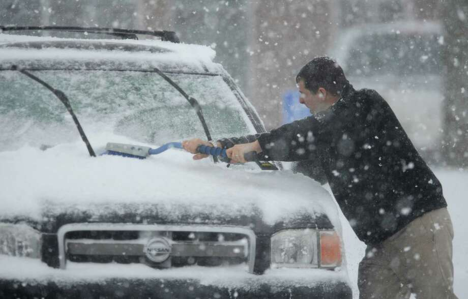 Keith Murzin, of Trumbull, brushes snow off his car at Big Y in Newtown, Conn. Thursday, Feb. 13, 2014.  Danbury and its surrounding areas are expected to see 14 to 20 inches of snow, which is expected to taper off around midnight. Photo: Tyler Sizemore / The News-Times