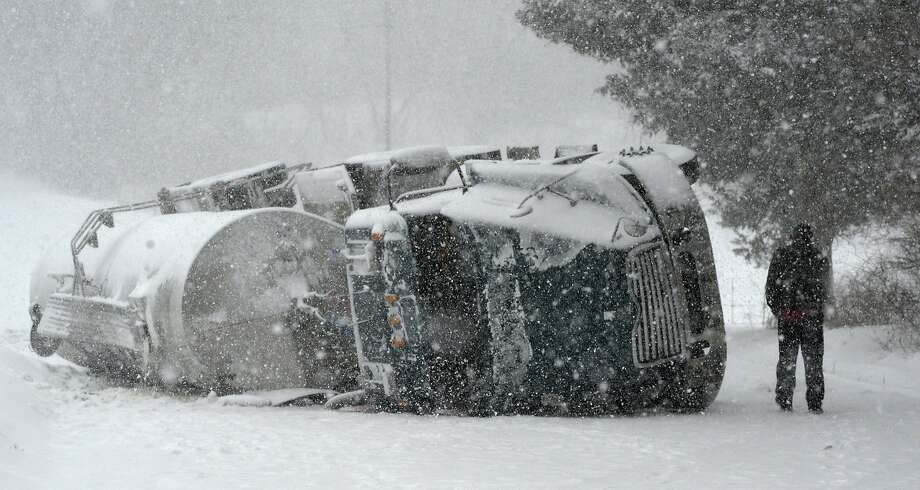 An overturned milk truck sits in the middle of Bridge Road Thursday afternoon Feb. 13, 2014, as the driver returns to his vehicle in Bethlehem, N.Y. after being interview by police at the scene.  Photo: Skip Dickstein, ALBANY TIMES UNION