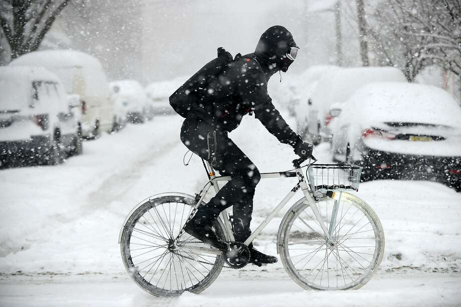 A man wearing ski goggles rides his bike on Broadway in Bayonne, N.J. on Thursday, Feb. 13, 2014. A storm spread heavy snow and sleet along the Northeast corridor, while power was out to hundreds of thousands in the ice-encrusted South. Photo: Reena Rose Sibayan, Associated Press